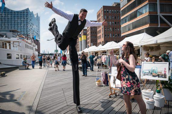 Sir Julian begrüsst Ihre Gäste ganz gross. Der Stelzenriese ist ein überragender Blickfang für Ihren Empfang. Auf Stadtfesten, Jubiläen und Festivals hebt er die Stimmung auf das hohe Niveau Ihrer Veranstaltung. Der Walk-Act verblüfft grosses und kleines Publikum mit Stelzen Akrobatik auf Riesen-Schritten. Ein Comedy Walk-Act der Spitzenklasse auf Ihrer Firmen Gala. Hier beim Traditionsschiff-Hafen beim Hafengeburtstag in Hamburg ein toller Blickfang auch neben der Elbphilharmonie.