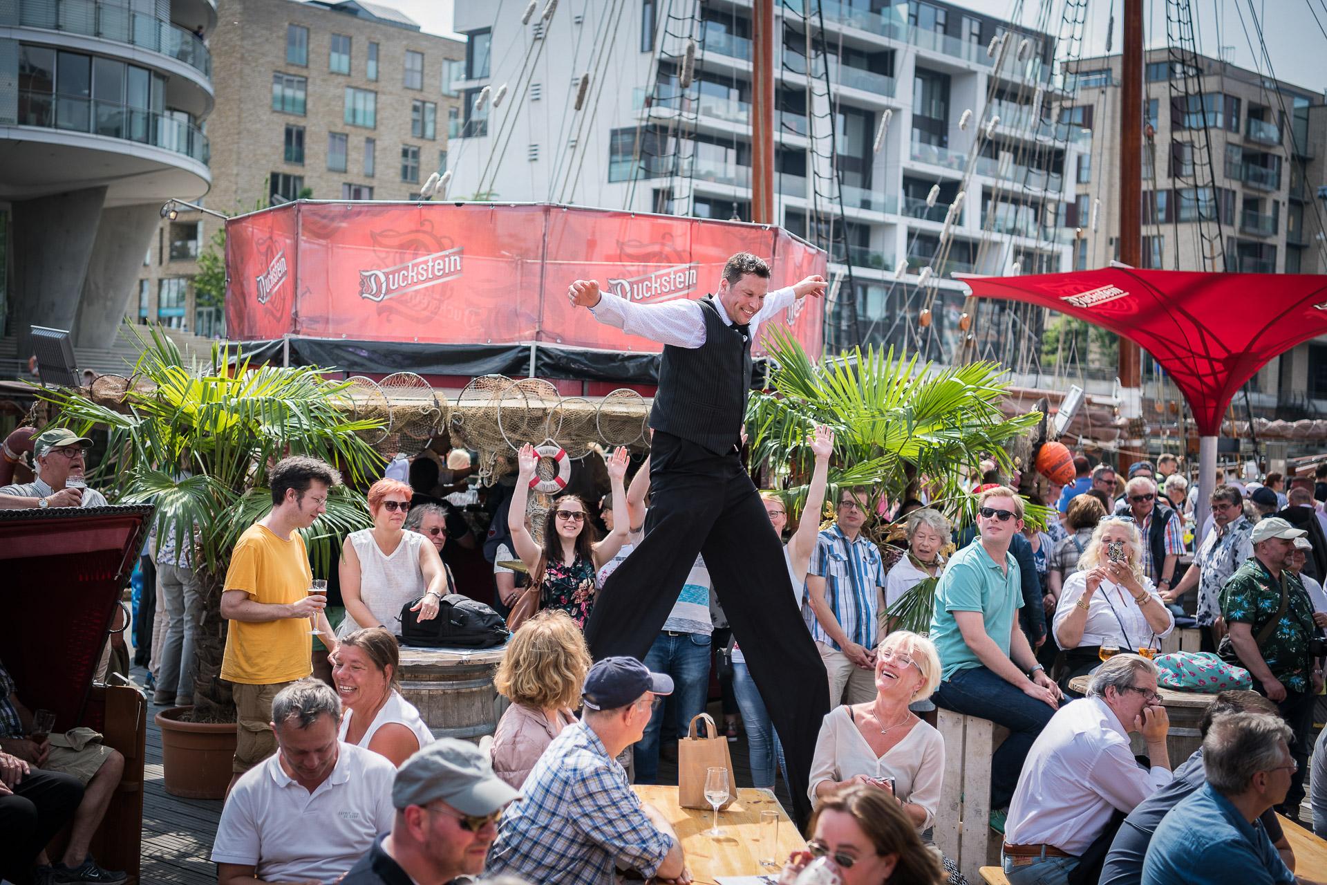 Sir Julian begrüsst Ihre Gäste ganz gross. Der Stelzenman ist ein überragender Blickfang für Ihren Empfang. Auf Stadtfesten, Jubiläen und Festivals hebt er die Stimmung auf das hohe Niveau Ihrer Veranstaltung. Der Stelzen Walk-Act verblüfft grosses und kleines Publikum mit Stelzen Akrobatik auf Riesen-Schritten. Ein Comedy Walk-Act der Spitzenklasse auf Ihrer Firmen Gala. Hier beim Traditionsschiff-Hafen beim Hafengeburtstag in Hamburg ein toller Blickfang auch neben der Elbphilharmonie. #willkommenimspass
